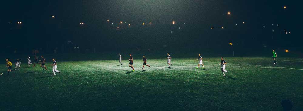 Fussballspieler auf einem Fussballplatz in dunklen unter Flutlicht